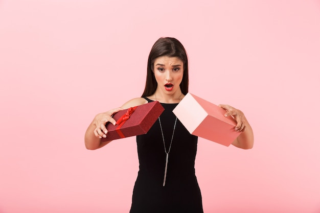 분홍색 배경 위에 절연 빈 선물 상자를 들고 검은 드레스를 입고 화가 여자