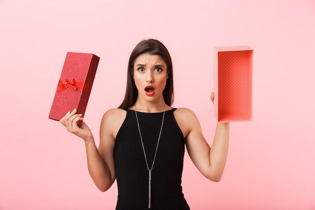 ピンクの背景に分離された空のギフトボックスを保持している黒いドレスを着て動揺する女性