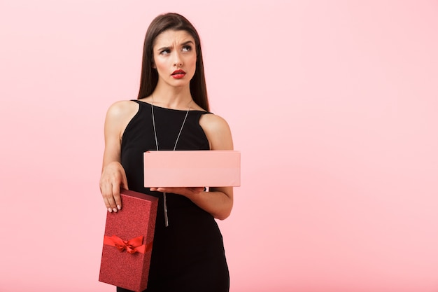 Upset woman wearing black dress holding empty gift box isolated over pink background