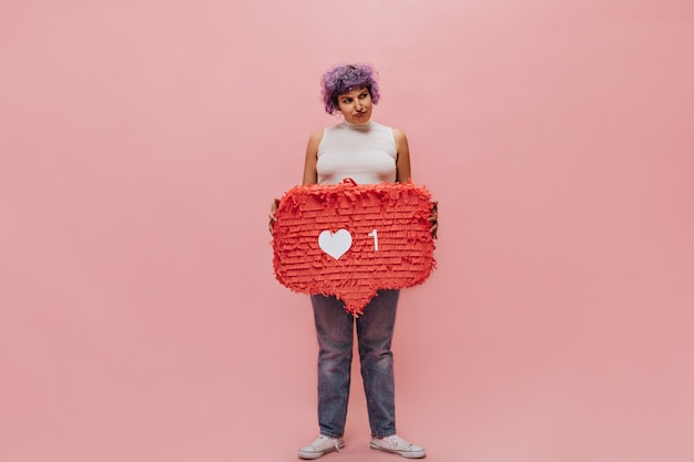 Upset woman in white top, blue jeans and light sneakers looks away and holds huge red sign like on isolated pink.