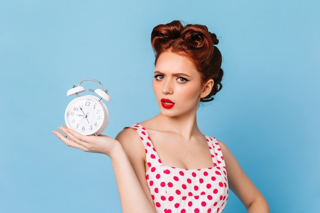 Upset woman with bright makeup showing time. studio shot of beautiful pinup girl with clock.