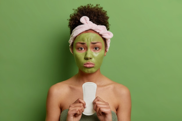 Upset woman with curly hair applies nourishing beauty mask on face holds sanitary napkin has mestruation suffers from pain wrapped in towel isolated over green wall