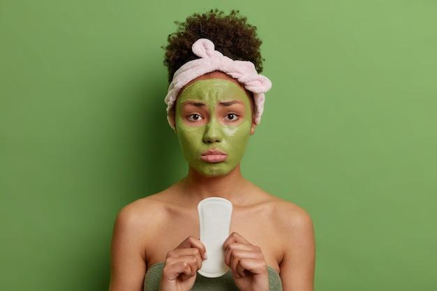 巻き毛の動揺した女性は、顔に栄養のある美容マスクを適用し、生理用ナプキンを保持し、緑の壁に隔離されたタオルに包まれた痛みに苦しんでいます