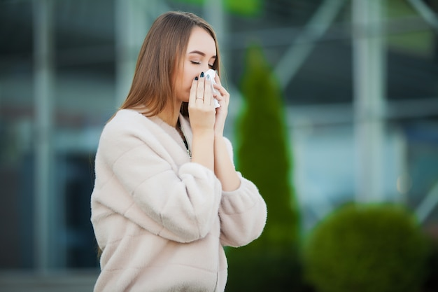 Upset woman with flu and tissues outdoors
