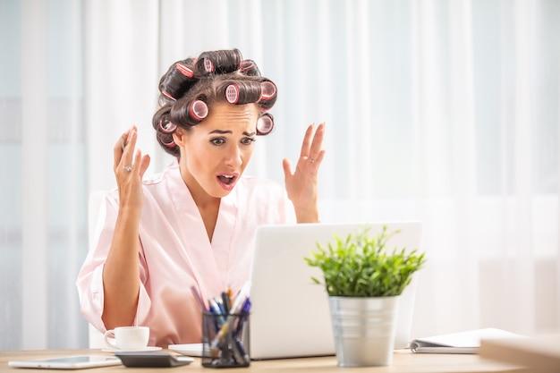 머리 롤러와 나이트 드레스를 입은 화난 여성이 놀란 표정으로 노트북 화면을 쳐다봅니다.