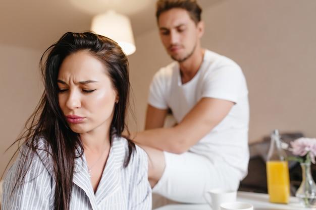 Donna sconvolta con capelli lisci castani in posa a casa con uomo triste sullo sfondo