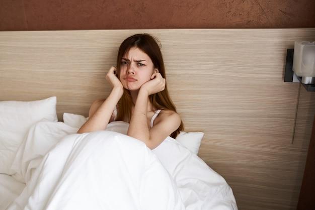 動揺した女性は、白い毛布の下のベッドで朝早く目が覚めた