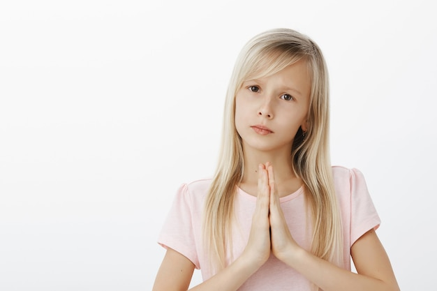 Upset worried little girl asking friend for forgiveness. sad cute daughter with fair hair in pink t-shirt, holding hands in pray, begging or apologizing for bad behaviour