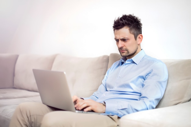 Upset and worried young businessman sitting and working at laptop