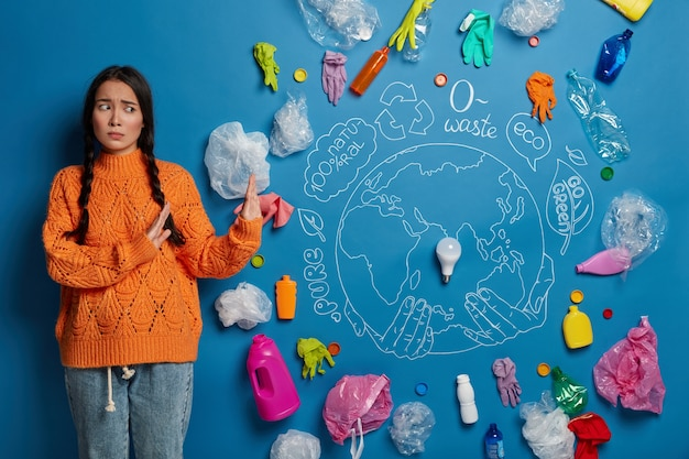 Upset worried young girl in casual clothes shows no gesture against plastic waste, gestures against blue background with drawn globe