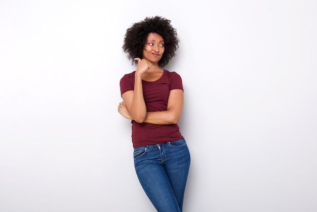 Upset young african woman pointing backwards with her thumb on white background