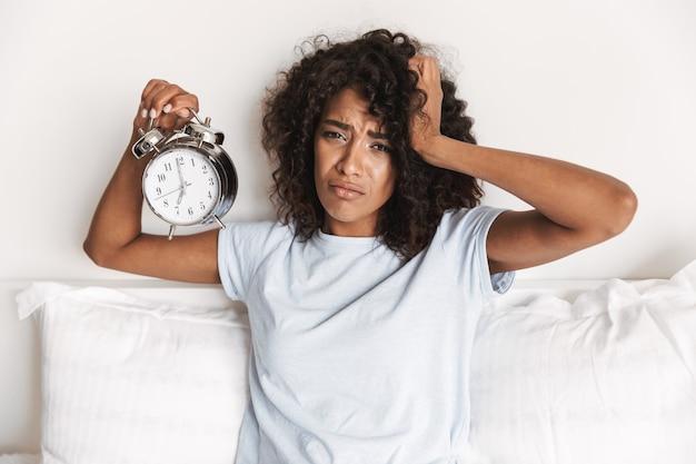 目覚まし時計を示す動揺した若いアフリカの女性