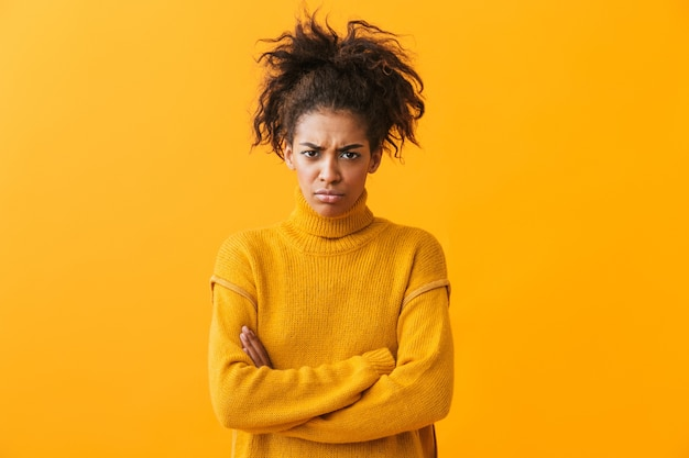 Upset young african woman wearing sweater standing isolated
