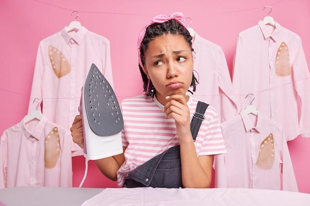 Расстроенная молодая афроамериканка-домработница с дредами грустно смотрит в сторону, не хочет гладить одежду, держит электрический утюг, носит полосатую футболку с повязкой на голову и комбинезон, уставшая от работы по дому.