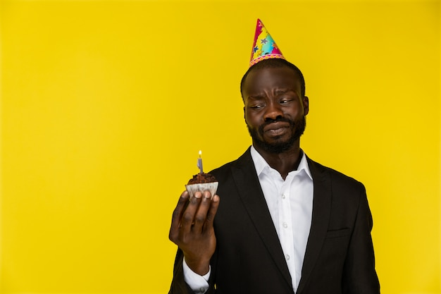Upset young afroamerican guy in black suit and birthday hat with burning candle