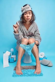 Sconvolto giovane donna asiatica soffre di crampi mestruali pose in toilette tiene il tampone utilizza il miglior assorbente indossa accappatoio e maschera per dormire isolato sul muro blu
