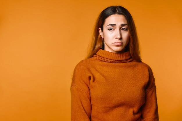 Расстроенная молодая привлекательная кавказская девушка одета в пуловер