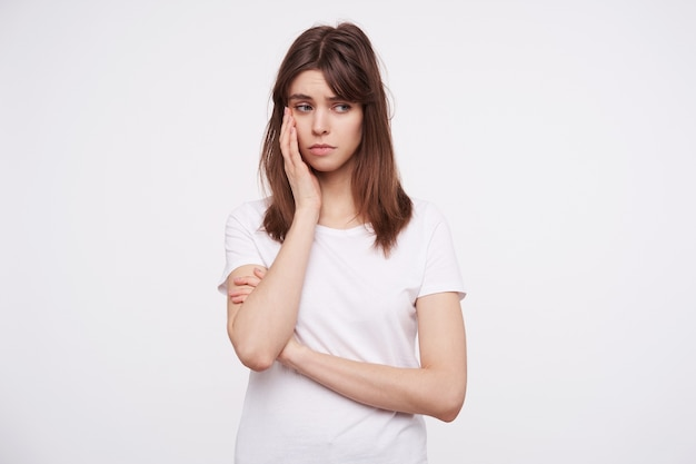 Upset young attractive dark haired woman with casual hairstyle keeping raised palm on her cheek and looking sadly aside, dressed in white basic t-shirt while posing over white wall