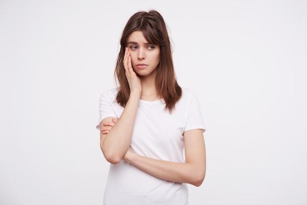 Расстроенная молодая привлекательная темноволосая женщина с повседневной прической, держащая приподнятую ладонь на щеке и печально смотрящую в сторону, одетая в белую простую футболку, позирует над белой стеной