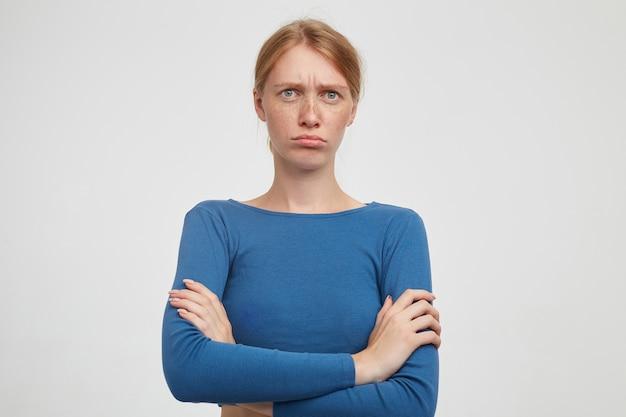 Sconvolto giovane donna attraente con acconciatura casual incrocio le mani sul petto mentre posa su sfondo bianco, sopracciglia accigliate e labbra pieghevoli mentre guarda la fotocamera
