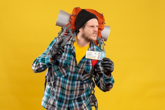 飛行機のチケットを持っている黒い帽子をかぶった若いバックパッカーを怒らせる