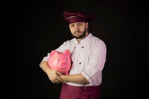 Расстроенный молодой бородатый шеф-повар в униформе держит приклеенную копилку