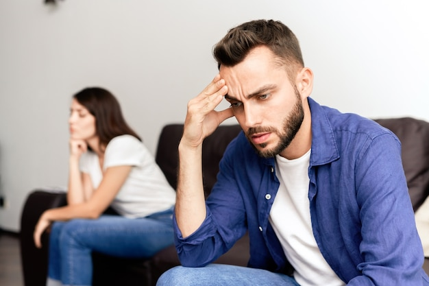 Upset young bearded man in blue shirt sitting on side opposite to girlfriend and rubbing forehead while suffering about fight