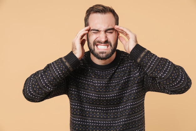 Расстроенный молодой бородатый мужчина в теплом свитере стоит изолированно над бежевой стеной и страдает от головной боли