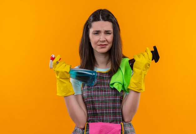Sconvolto giovane bella ragazza in grembiule e guanti di gomma che tengono spray per la pulizia con espressione triste sul viso