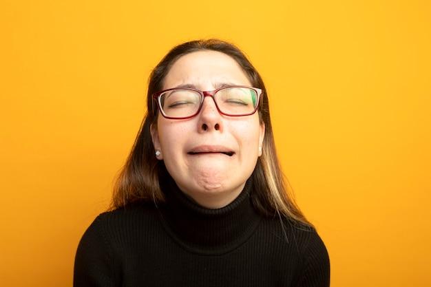 泣いている黒いタートルネックの動揺した若い美しい少女