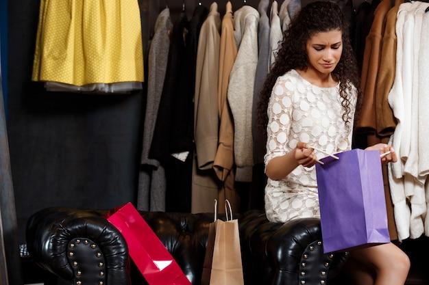 Расстроен молодая красивая девушка, сидя в торговом центре с покупками.