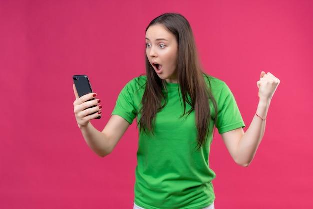 Sconvolto giovane bella ragazza che indossa la maglietta verde che tiene smartphone guardando lo schermo stupito e sorpreso in piedi su sfondo rosa isolato
