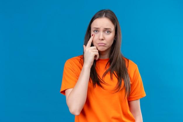 孤立した青い背景の上に立っている悲しそうな表情でカメラを見て彼女の目に指で指しているオレンジ色のtシャツを着ている動揺の美しい少女