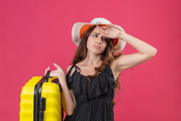 Ragazza giovane bella viaggiatore sconvolto in vestito a pois in cappello estivo che tiene la valigia che guarda l'obbiettivo con espressione triste sul viso in piedi su sfondo rosa