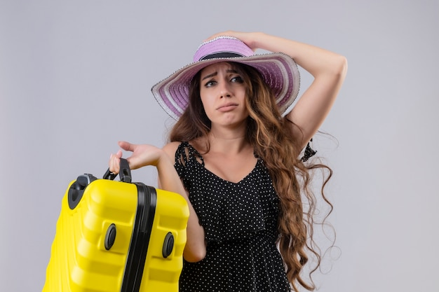 Upset young beautiful traveler girl in dress in polka dot in summer hat holding suitcase looking at camera with sad expression on face standing over white background