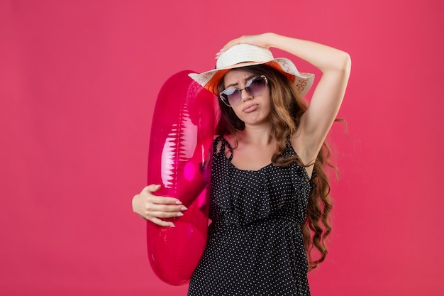 Ragazza giovane bella viaggiatore sconvolto in vestito a pois in cappello estivo indossando occhiali da sole che tiene anello gonfiabile che guarda l'obbiettivo con espressione triste sul viso in piedi su sfondo rosa