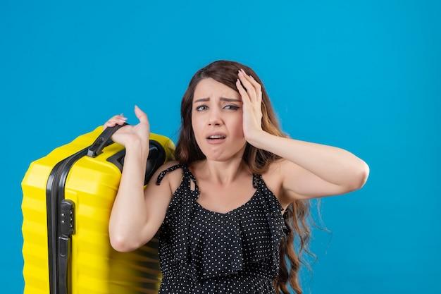 Расстроенная молодая красивая девушка-путешественница в платье в горошек, держащая чемодан, смотрит в камеру с грустным выражением лица, стоя на синем фоне