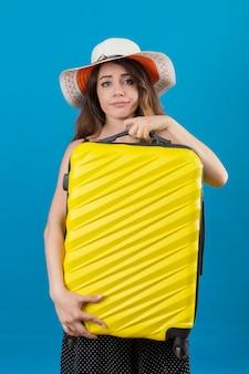 Расстроенная молодая красивая девушка-путешественница в платье в горошек в летней шляпе держит чемодан, глядя в камеру с грустным выражением лица, стоя на синем фоне