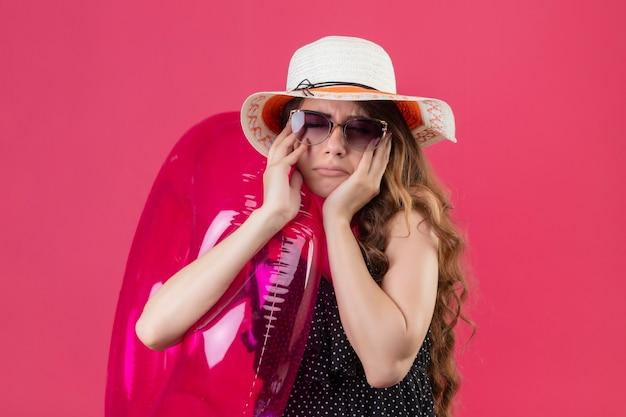 ピンクの背景の上の顔に悲しそうな表情で立っているインフレータブルリングを保持しているサングラスを身に着けている夏帽子の水玉のドレスで動揺の若い美しい旅行者の女の子