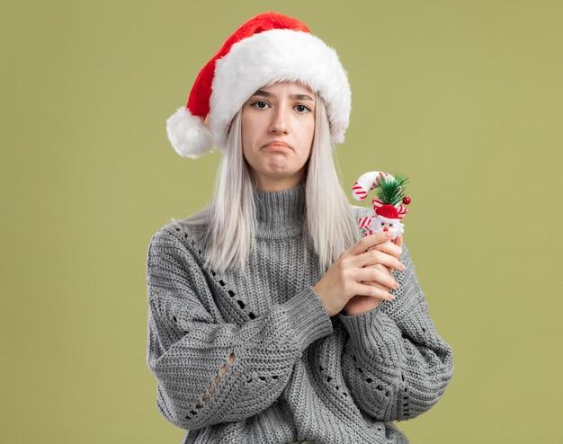 Sconvolto giovane donna bionda in maglione invernale e cappello da babbo natale che tiene un bastoncino di zucchero natalizio con un'espressione triste sul viso che increspa le labbra in piedi sul muro verde