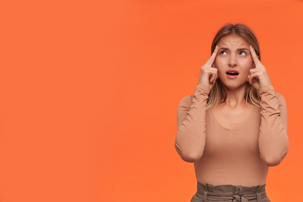 オレンジ色の壁に隔離された、こめかみに手を上げて混乱して上向きに見えるカジュアルな髪型の若い青い目の短い髪のブロンドの女性を動揺させます