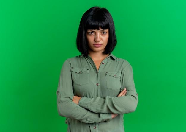 Sconvolto la giovane ragazza caucasica castana sta con le braccia incrociate isolato su priorità bassa verde con lo spazio della copia