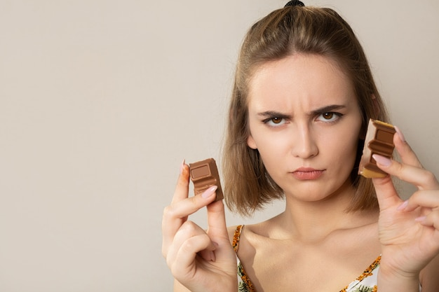 チョコレートのかけらを持っている若いブルネットの女性を動揺させます。テキスト用のスペース