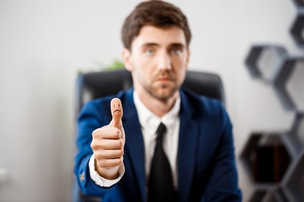 Расстроен молодой бизнесмен, показывая хорошо на рабочем месте.