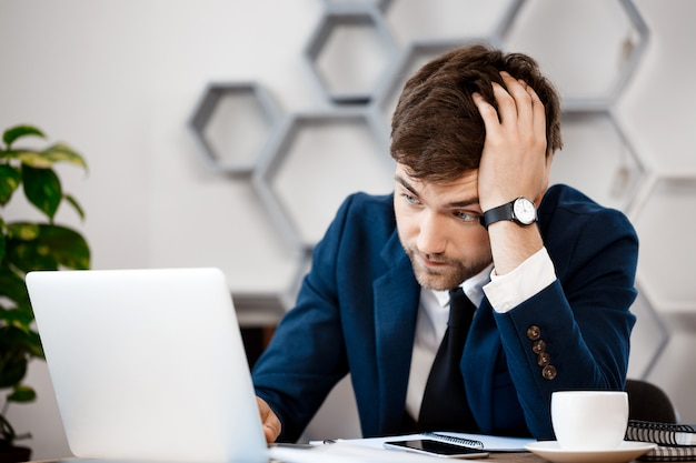 Upset young businessman sitting at laptop, office background.