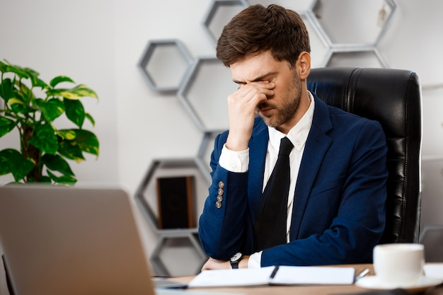 Upset young businessman sitting at workplace, office background.