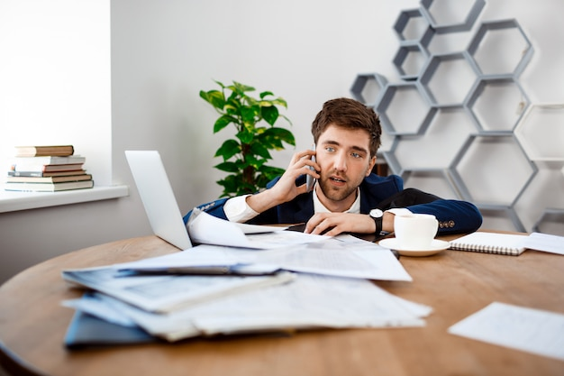 Upset young businessman speaking on phone, office background.
