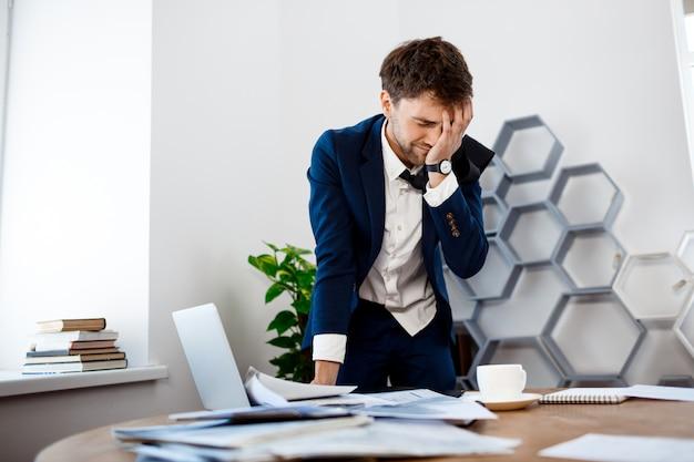 Расстроен молодой бизнесмен, стоя на рабочем месте, офис фон.