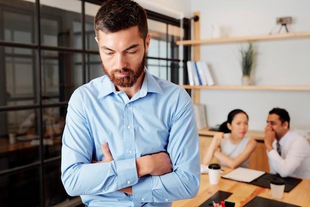 Расстроенный молодой бизнесмен, стоящий в закрытой позе, коллеги сплетничают о нем на заднем плане