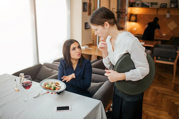 Upset young businesswoman complain about bowl with salad